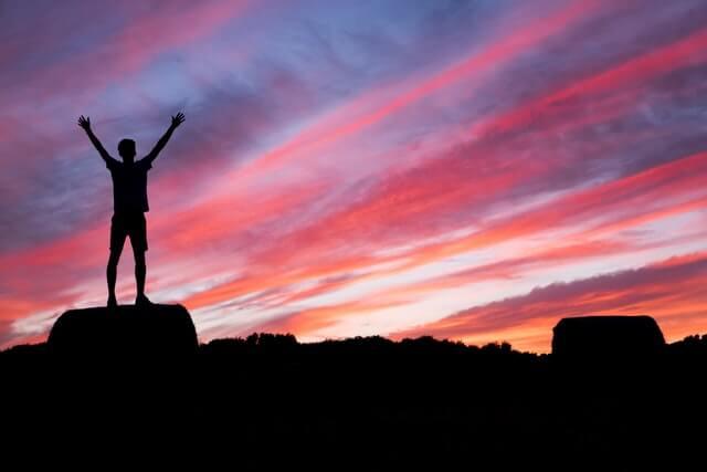 両手を挙げる男性と夕焼け空
