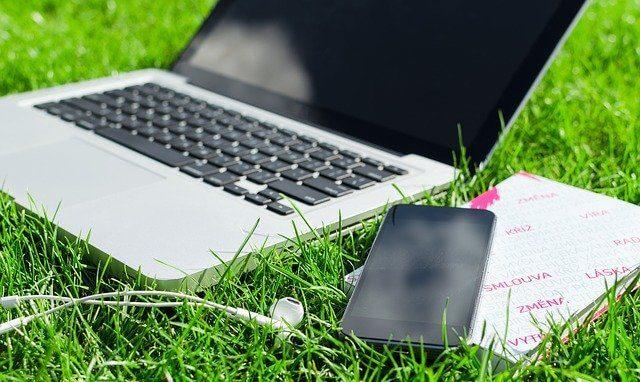 人工芝の上のパソコンとスマートフォン